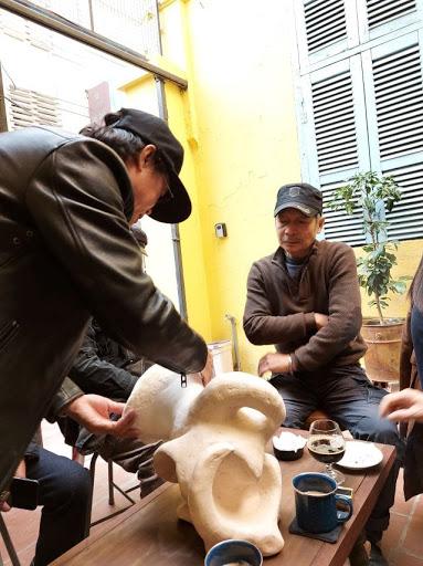 Họa sĩ Đinh Phong (trái) đang giới thiệu một tác phẩm của mình vừa nung xong với điêu khắc gia nổi tiếng Đào Châu Hải.